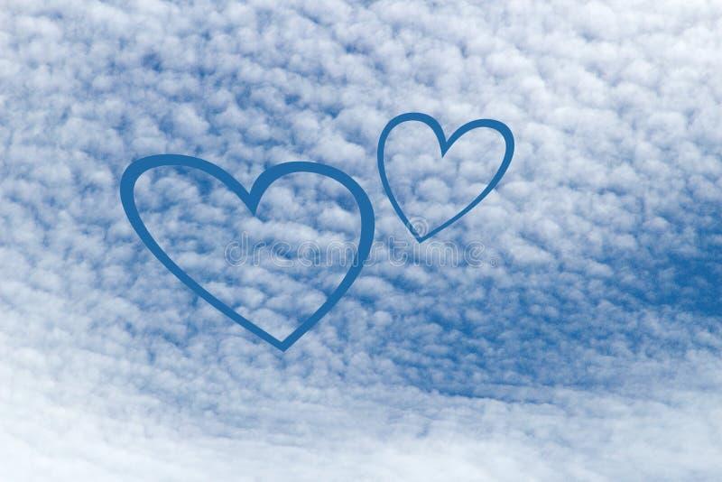 Símbolo de dois corações feitos das nuvens em um céu azul fotos de stock royalty free