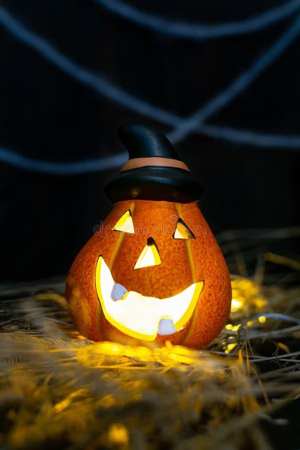 Símbolo de Halloween - brillante cabeza de calabaza de Jack o`Lantern con una lámpara en un sombrero negro puntiagudo en el heno fotos de archivo