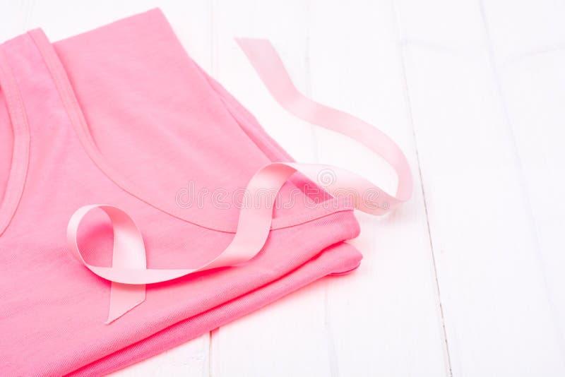 Símbolo de la atención sanitaria y de la medicina - cinta rosada de la conciencia del cáncer de pecho en la camisa femenina imagen de archivo libre de regalías