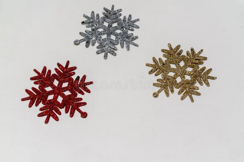 Símbolo de la escama de la nieve con brillo en rojo, plata y oro para el ornamento y la decoración de la Navidad aislada en blanc imágenes de archivo libres de regalías