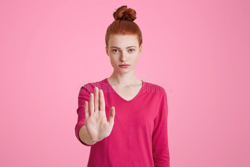 Símbolo de la prohibición Los gestos femeninos pecosos atractivos jovenes en estudio, demostraciones paran la muestra, rechazan h imagenes de archivo