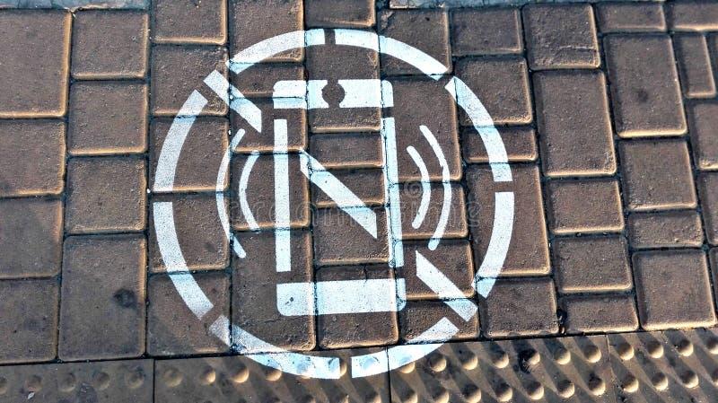 Símbolo de la prohibición para mirar el teléfono móvil, mientras que cruza el camino imagen de archivo
