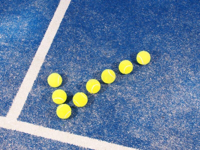 Símbolo de la señal de las pelotas de tenis una corte de hierba artificial azul prístina fotografía de archivo