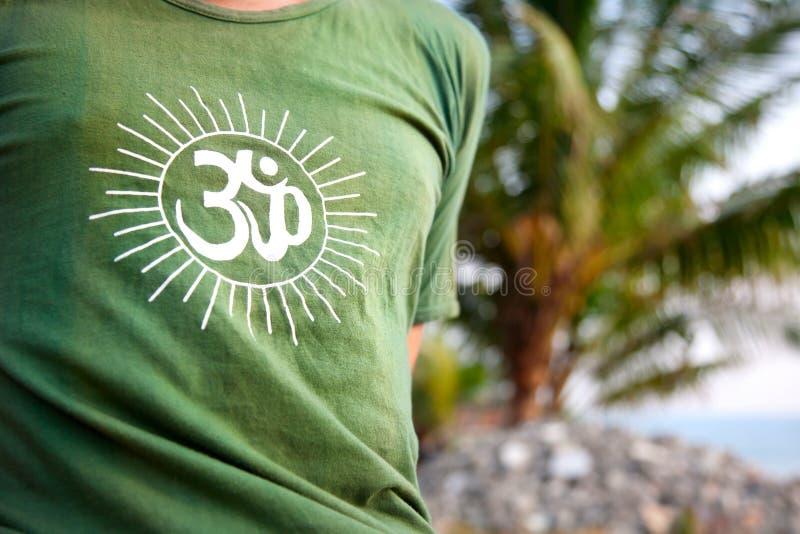 Símbolo de OM en la camiseta verde imagenes de archivo
