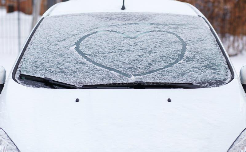 Símbolo del amor del corazón en el parabrisas del coche en nieve fotos de archivo libres de regalías
