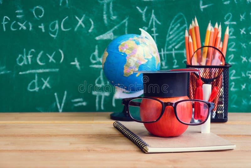 Símbolo del conocimiento de Apple y libros del lápiz en el escritorio con el tablero b fotografía de archivo