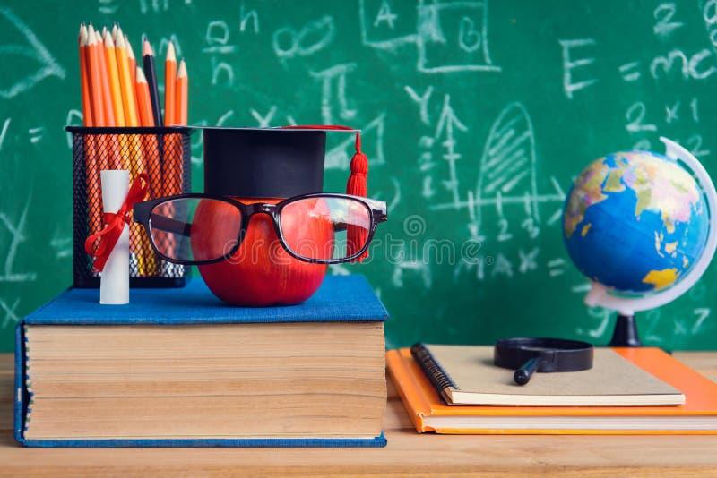 Símbolo del conocimiento de Apple y libros del lápiz en el escritorio con el tablero b imagen de archivo