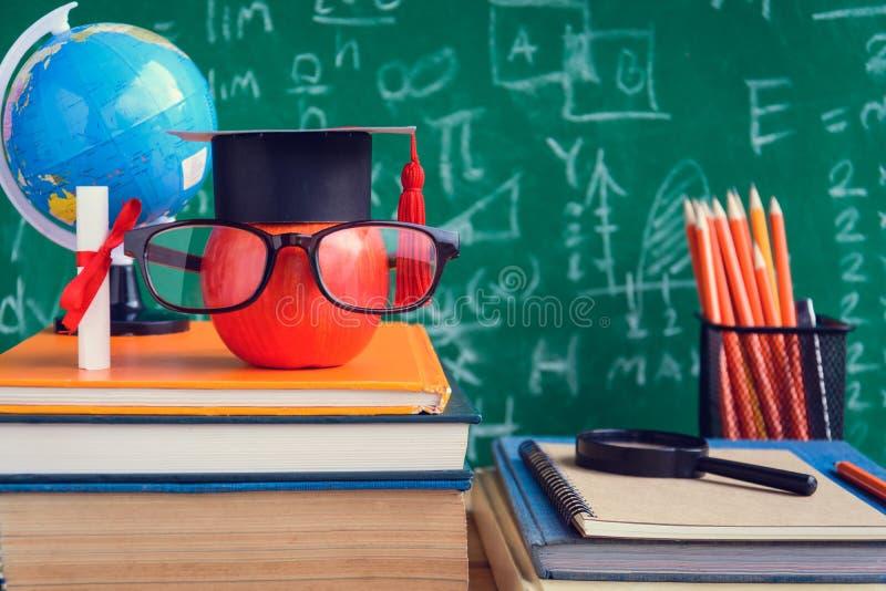 Símbolo del conocimiento de Apple y libros del lápiz en el escritorio con el tablero b foto de archivo