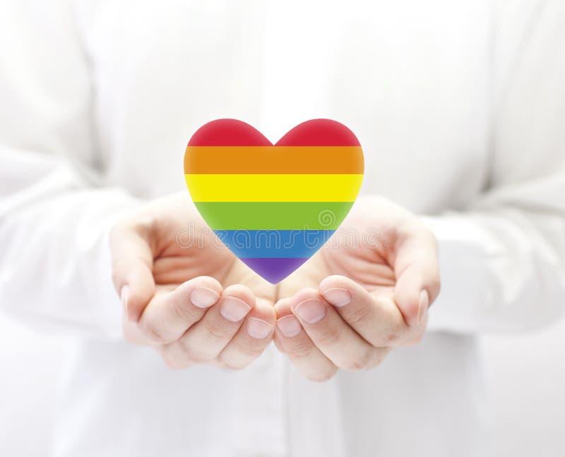 Símbolo del corazón del arco iris de LGBT del amor en manos fotos de archivo