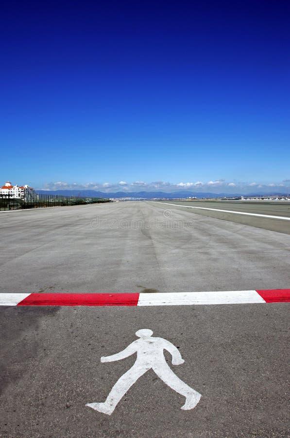 Símbolo del hombre que recorre en cauce en el aeropuerto de Gibraltar imagenes de archivo