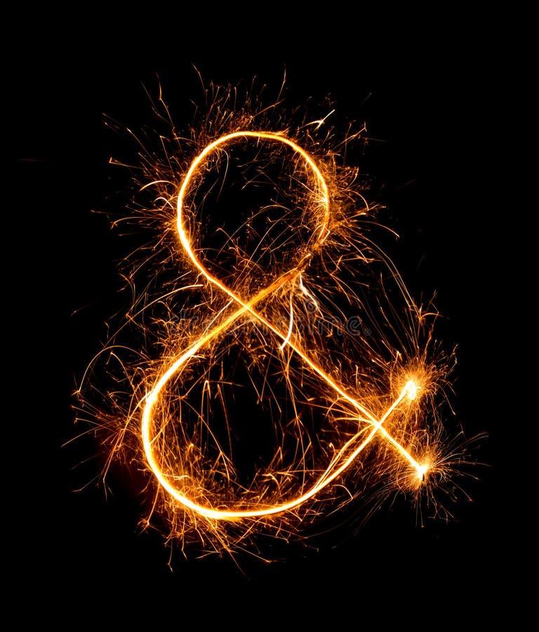 Símbolo do Ampersand feito de chuveirinhos do fogo de artifício na noite imagens de stock royalty free
