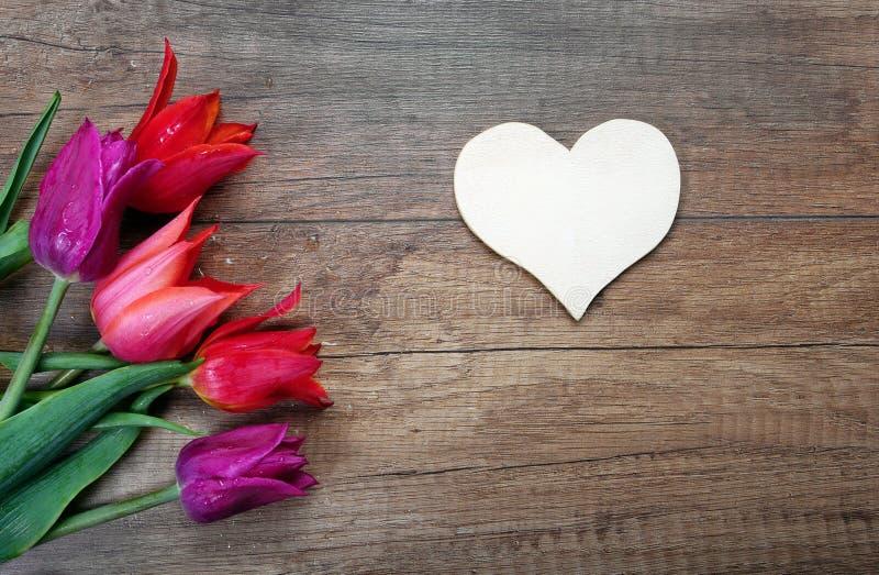 Símbolo do coração do amor e das tulipas em um fundo de madeira St Dia do ` s do Valentim Dia de matrizes Copie espaços fotografia de stock