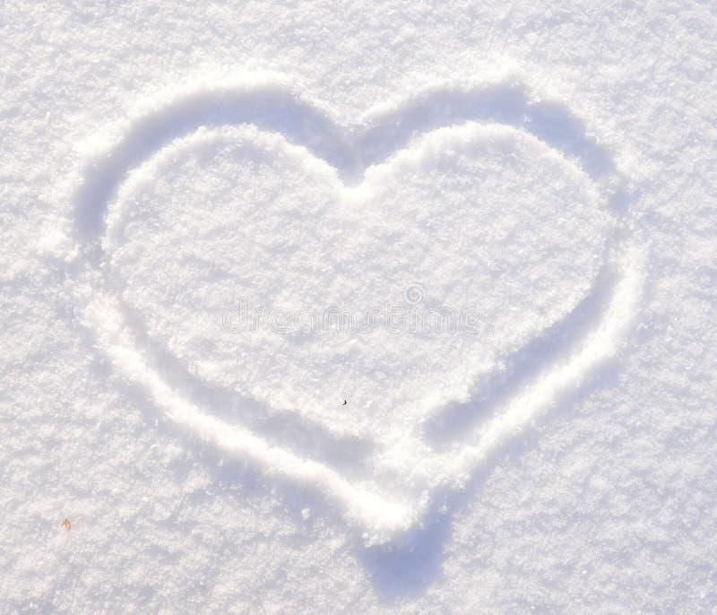 Símbolo do coração no fundo da textura fresca da neve Conceito do dia do ` s do Feliz Natal ou do Valentim Copie o espa?o para o  fotografia de stock