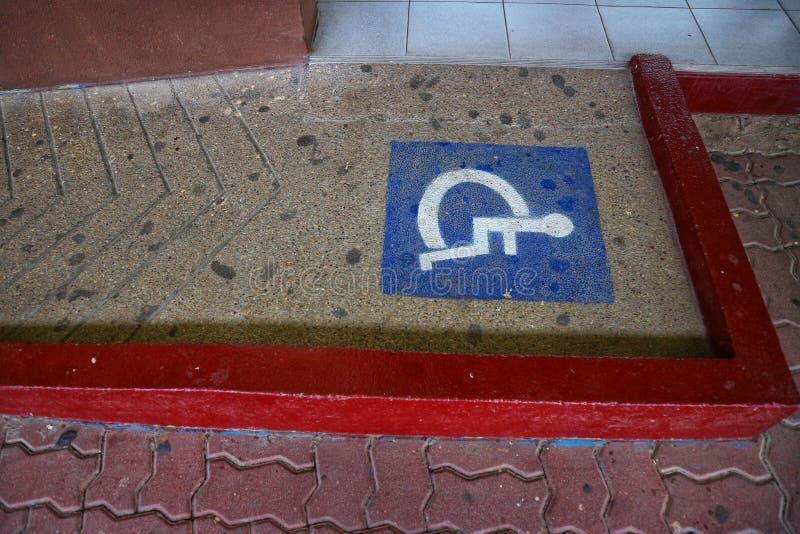 Símbolo do sinal na rampa da cadeira de rodas da cadeira de rodas do assoalho da passagem para os enfermos imagens de stock royalty free