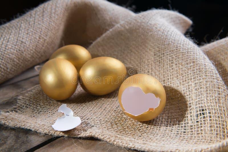 Símbolo do sucesso ou conceito feliz da Páscoa Ovo dourado grande quebrado vazio em um fundo natural de madeira rústico fotos de stock royalty free