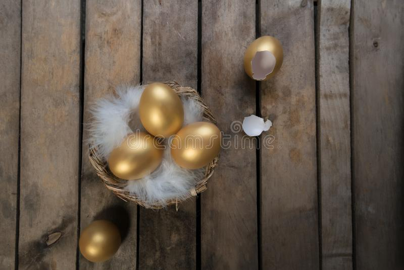 Símbolo do sucesso ou conceito feliz da Páscoa Ovo dourado grande quebrado vazio em um fundo natural de madeira rústico, vista su fotografia de stock