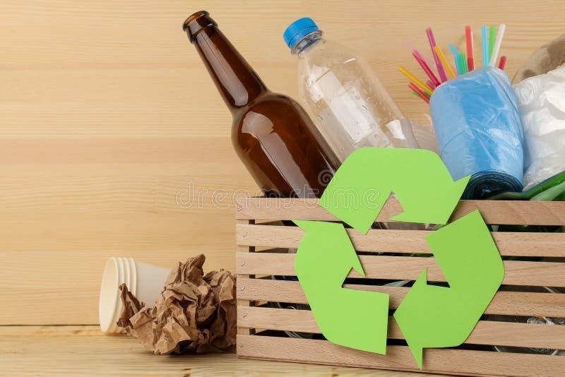 Símbolo e lixo de Eco na caixa recycling Reciclagem de resíduos no fundo de madeira natural imagens de stock royalty free