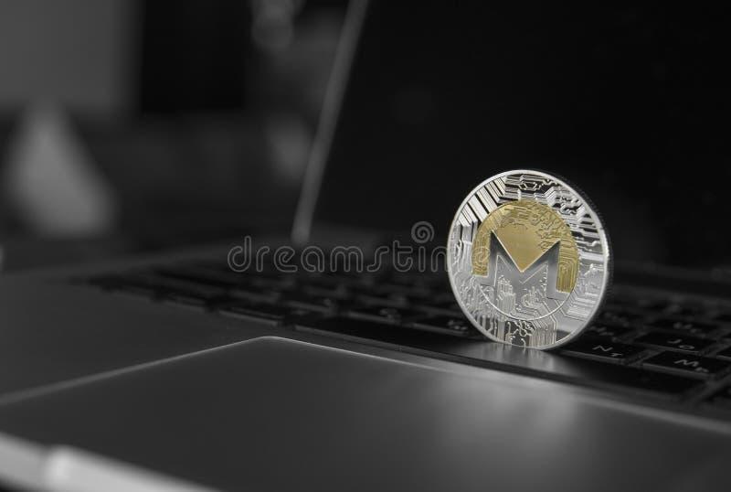 Símbolo en el ordenador portátil, moneda financiera del concepto futuro, muestra de la moneda de Monero de moneda crypto Explotac fotografía de archivo
