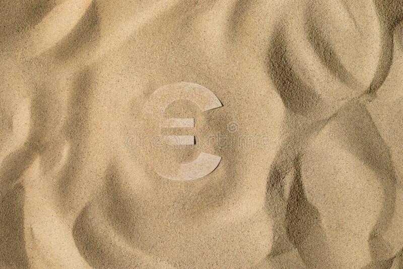 Símbolo euro debajo de la arena fotos de archivo
