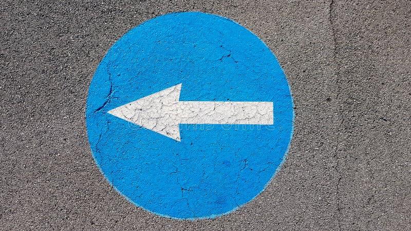 Símbolo izquierdo de la señal de tráfico del tráfico de la vuelta con la flecha blanca que señala izquierda foto de archivo libre de regalías