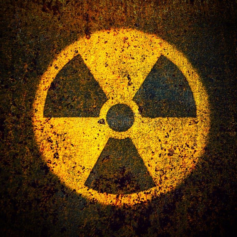 Símbolo radiactivo amarillo redondo del peligro de la radiación ionizante pintado en un fondo oxidado masivo de la pared del meta fotografía de archivo