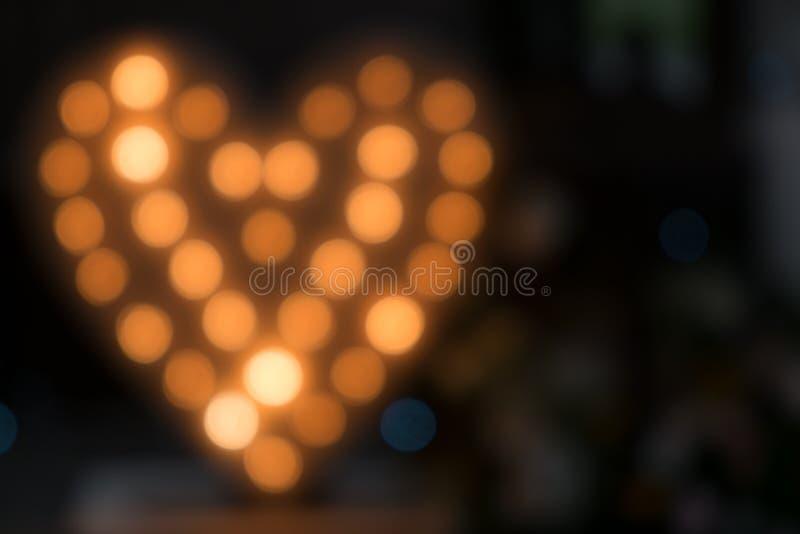 Símbolo Unfocused do coração com as ampolas de incandescência no fundo preto fotos de stock royalty free