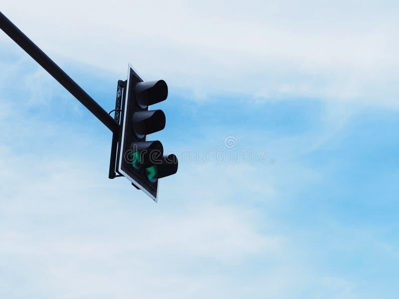 Símbolo verde de la flecha en el semáforo contra el cielo azul imagen de archivo libre de regalías