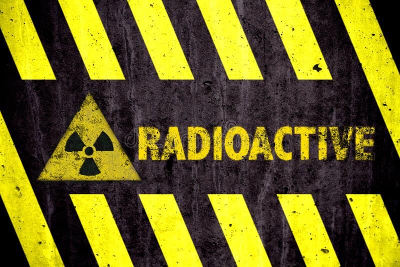 Símbolo y palabra con amarillo y rayas negras radiactivos del peligro de la radiación ionizante pintadas en un muro de cemento ma stock de ilustración