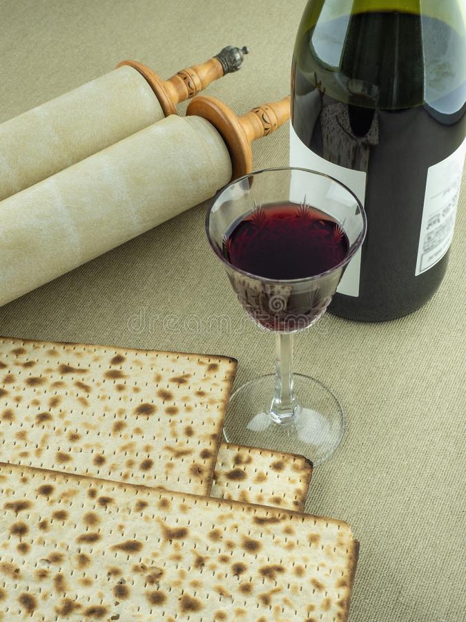 Símbolos de la pascua judía judía: Volutas de Torah, vino tinto en un vidrio y matzoh en un fondo de la lona fotos de archivo libres de regalías