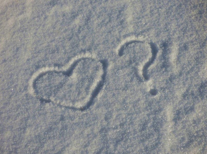 Símbolos del corazón y de la pregunta en la nieve Silueta rom?ntica de la muestra en la tierra del invierno fotografía de archivo