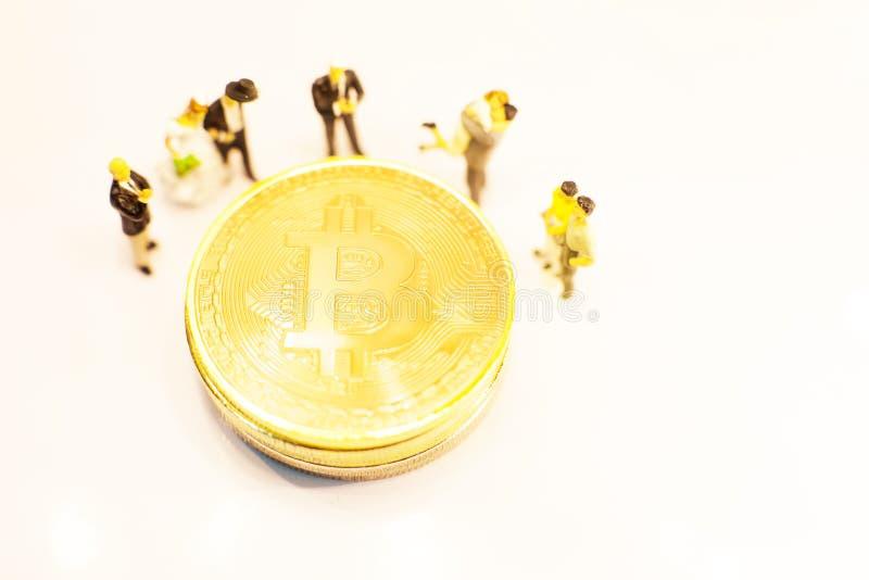 Símbolos del cryptocurrency de Bitcoin en el centro de la gente miniatura Los hombres de negocios se colocan alrededor de pila de foto de archivo libre de regalías