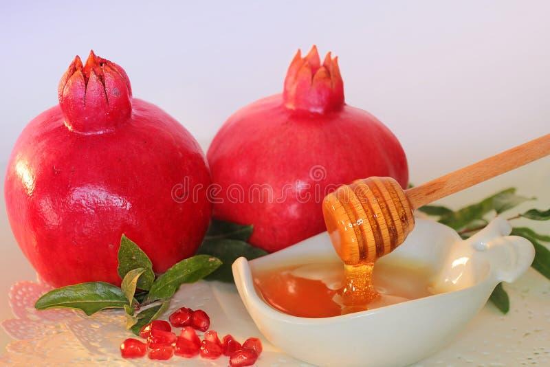 Símbolos do hashanah do rosh do feriado - mel e romã fotografia de stock