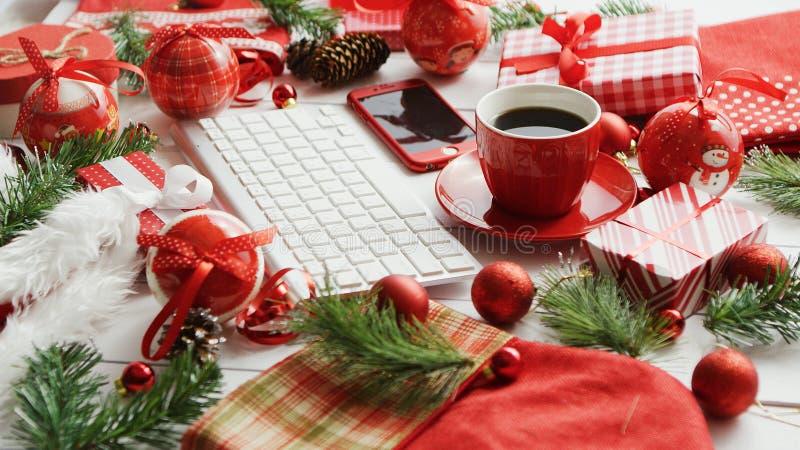 Símbolos do Natal em torno dos dispositivos e da bebida quente foto de stock