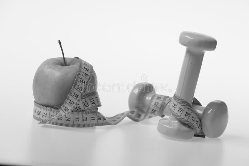 Símbolos do regime e da aptidão da saúde, foco seletivo Pesos e fita perto da maçã verde no fundo branco fotos de stock royalty free