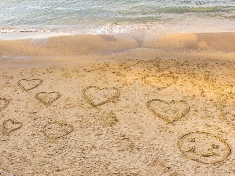 Símbolos dos corações e do desenho redondo da cara na areia na praia do telefone Baruch Passeio de Tel Aviv israel imagens de stock