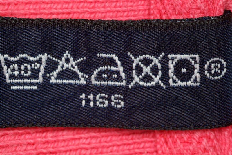 Símbolos en la ropa de la escritura de la etiqueta. Cierre para arriba. foto de archivo