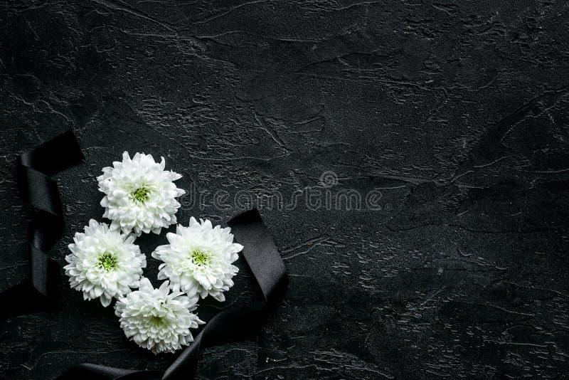 Símbolos fúnebres Flor blanca cerca de la cinta negra en espacio negro de la copia de la opinión superior del fondo imágenes de archivo libres de regalías