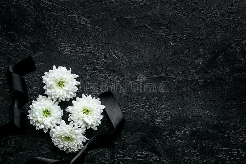 Símbolos fúnebres Flor branca perto da fita preta no espaço preto da cópia da opinião superior do fundo imagens de stock royalty free