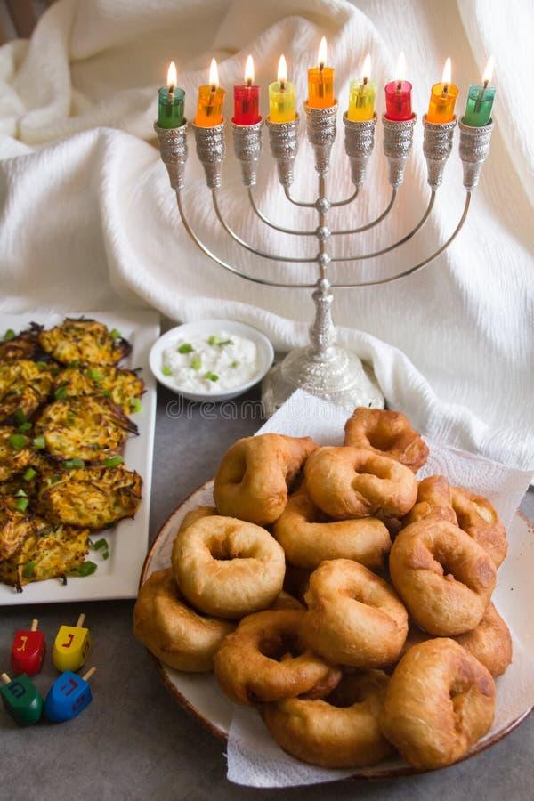Símbolos judíos de Jánuca del día de fiesta contra el fondo blanco; top de giro tradicional, candelabros tradicionales del menora foto de archivo