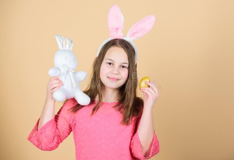 Símbolos y tradiciones de Pascua Niño juguetón con el juguete suave Día de fiesta de la primavera de la reunión El huevo de Pascu foto de archivo libre de regalías