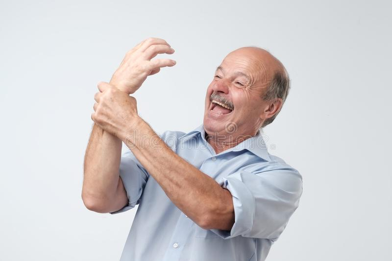 Síndrome estrangeira da mão Homem maduro que tenta controlar sua mão fotos de stock royalty free