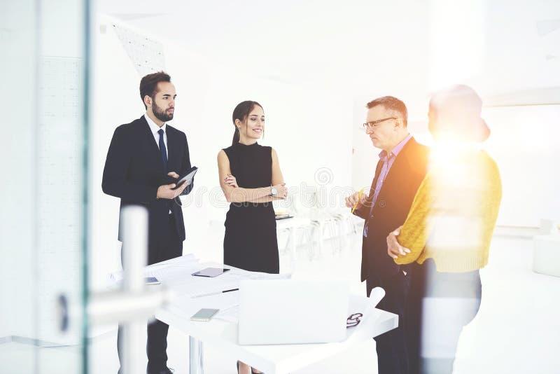 Sócios comerciais bem sucedidos na reunião do trabalho no escritório coworking imagem de stock