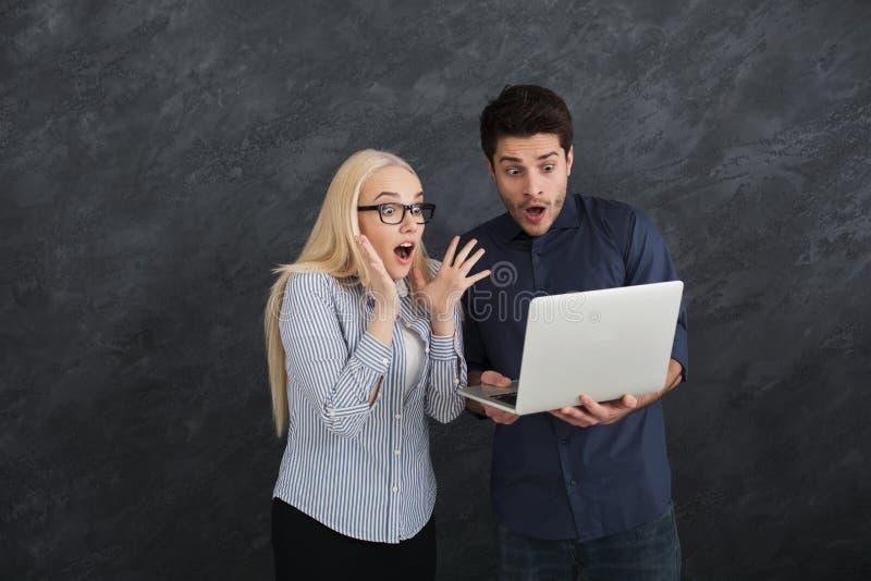 Sócios comerciais chocados que usam o portátil no estúdio foto de stock royalty free