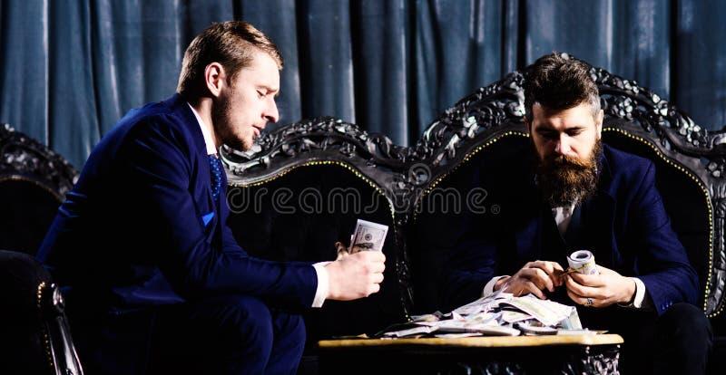 Sócios comerciais com caras sérias Criminosos em dólares elegantes da contagem dos ternos Lucro financeiro, interior luxuoso imagens de stock royalty free