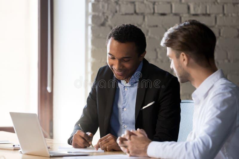 Sócios comerciais diversos após negociações bem sucedidas que assinam o contrato foto de stock