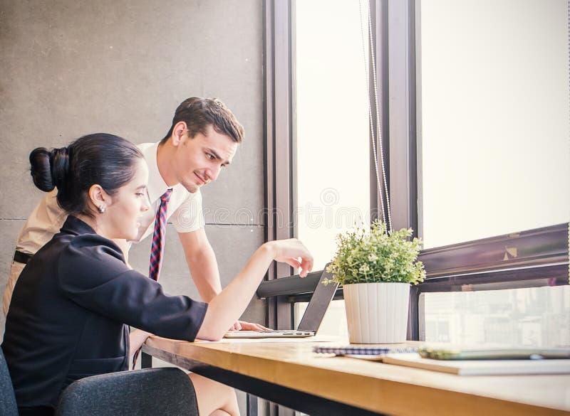 Sócios comerciais elegantes homem e mulher que escutam o colega na reunião imagens de stock