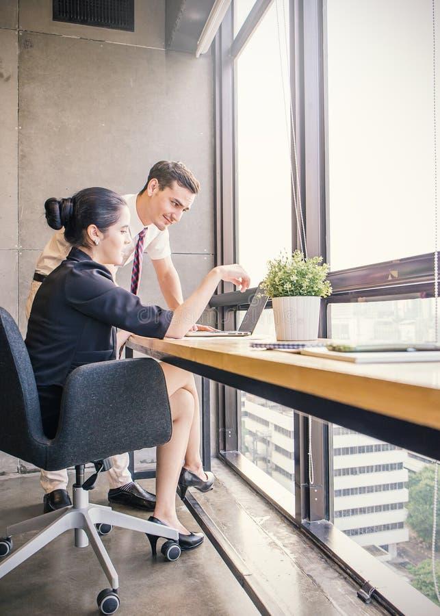 Sócios comerciais elegantes homem e mulher que escutam o colega na reunião foto de stock royalty free