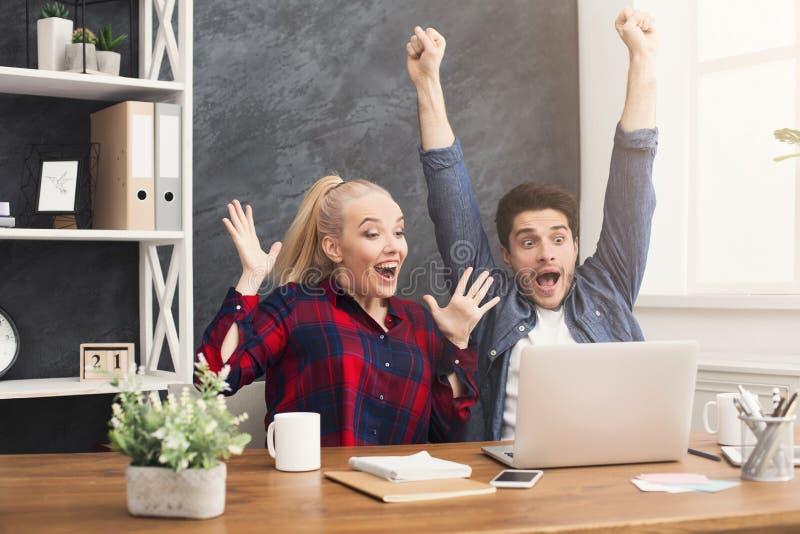 Sócios comerciais felizes novos no escritório com computador foto de stock