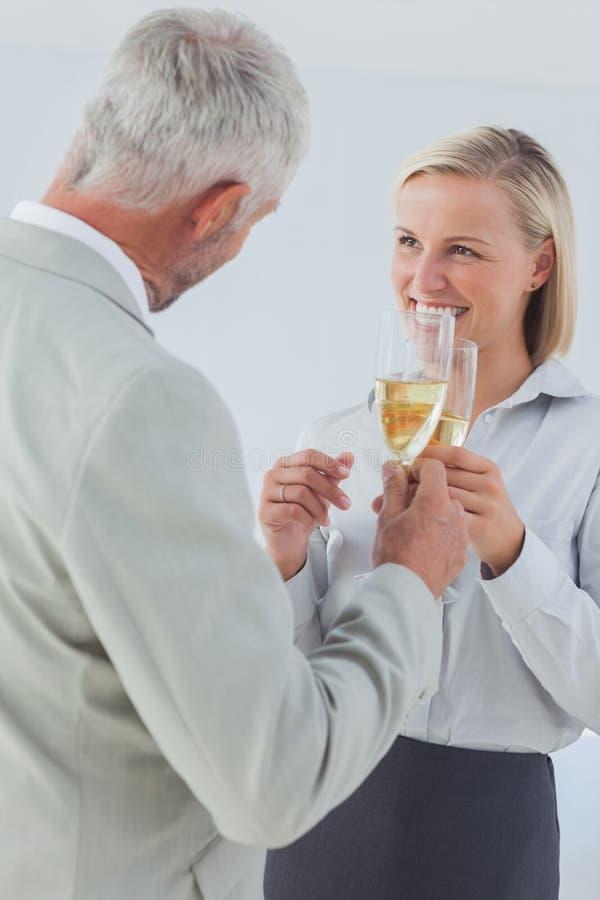Sócios comerciais felizes que brindam com champanhe imagens de stock royalty free