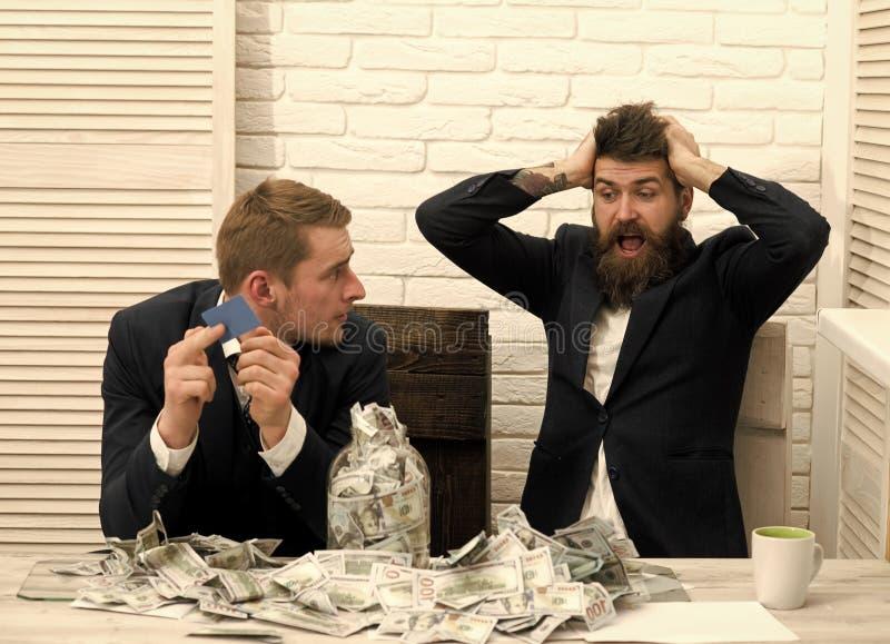 Sócios comerciais, homens de negócios na reunião no escritório O chefe farpado aturdido pelo lote do dinheiro, colega guarda o ca fotos de stock royalty free